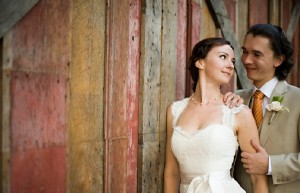 Married couple next to rustic barn
