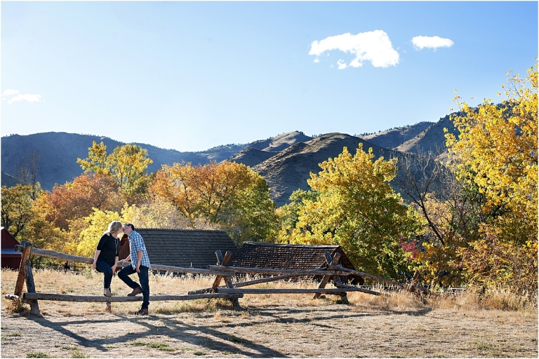 couple sitting on fence with trees and mountains, clear creek history park, golden colorado engagement session, autumn engagement session, l elizabeth events, colorado engagement photography, mountain engagement photographer