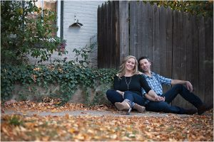couple sitting on ground with fall leaves, old wood house,clear creek history park, golden colorado engagement session, autumn, l elizabeth events, colorado engagement photography, mountain engagement photographer