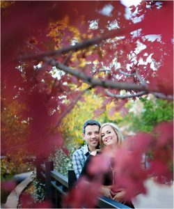 couple smiling behind red tree,clear creek history park, golden colorado engagement session, autumn, l elizabeth events, colorado engagement photography, mountain engagement photographer