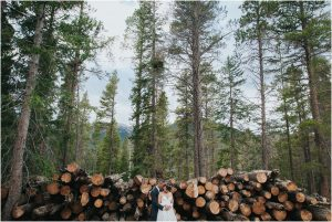 bride and groom in front of cut logs,mountain wedding planner, dao house, estes park, colorado wedding planning