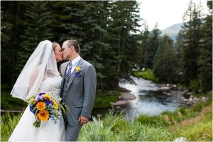 bride and groom portrait in front of river, purple and yellow floral, bridal bouquet, boutonniere, checkered tie, gray suit, donavan pavilion vail, colorado wedding photography, mountain wedding photographer