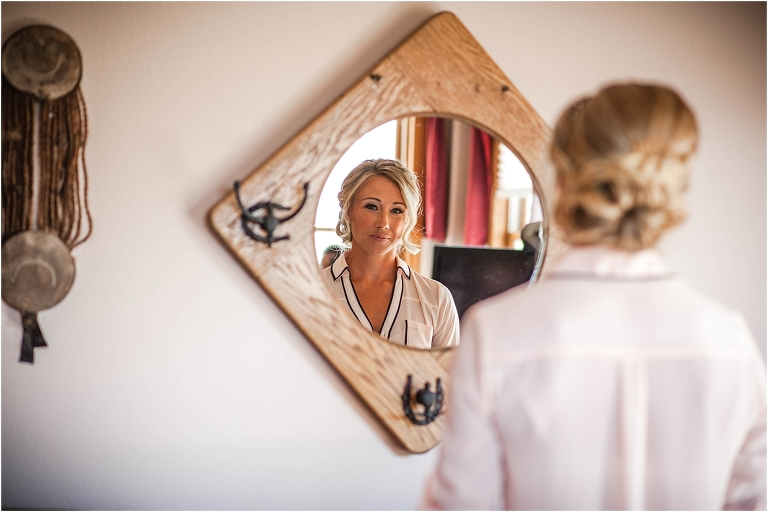 getting ready, bride in robe looking at reflection, hotel room, steamboat springs, colorado wedding photographer, mountain wedding photography