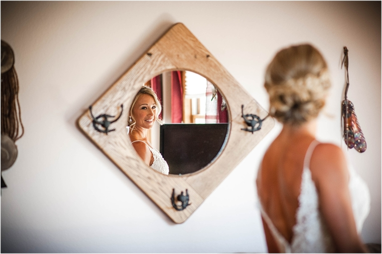 getting ready, wedding dress, bride looking in mirror, hotel room, steamboat springs, colorado wedding photographer, mountain wedding photography