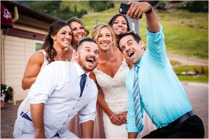 wedding guests taking selfie with bride, wedding reception, steamboat springs resort, colorado wedding photographer