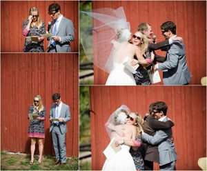 readings, outdoor ceremony in front of rustic red barn at clear creek history park, golden colorado, wedding photographer, colorado wedding planner, bride's veil blowing in the wind, hugging