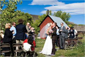 bride and groom kissing, recessional,wedding guests, outdoor ceremony in front of rustic red barn at clear creek history park, golden colorado, wedding photographer, colorado wedding planner