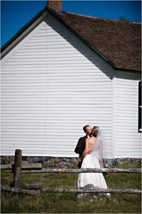 bride and groom portraits, kissing in front of rustic white barn,clear creek history park, golden colorado, wedding photographer, colorado wedding planner