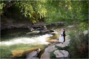 bride and groom portrait along clear creek in golden, river, wide angle, colorado wedding planner, mountain wedding photographer