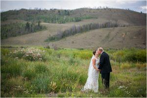 bride and groom kissing in field,C Lazy U Ranch, Granby, Colorado, Rustic Ranch Wedding, Colorado Wedding Planner, Mountain Wedding Photographer