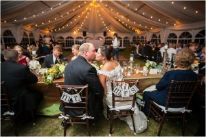 bride and groom kissing at their seats, tented reception,C Lazy U Ranch, Granby, Colorado, Rustic Ranch Wedding, Colorado Wedding Planner, Mountain Wedding Photographer